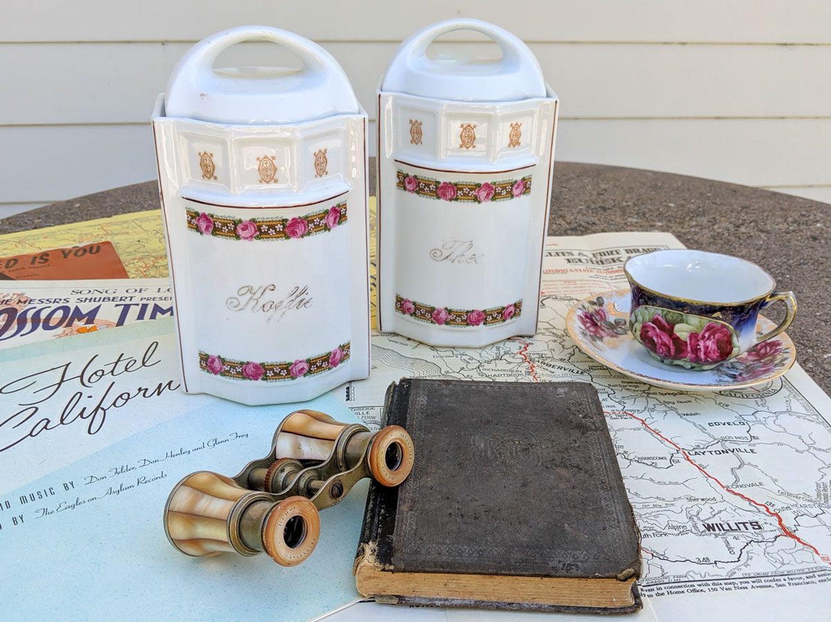 vintage ceramics are set on a table with vintage maps, sheet music, a school reader and some vintage opera glasses
