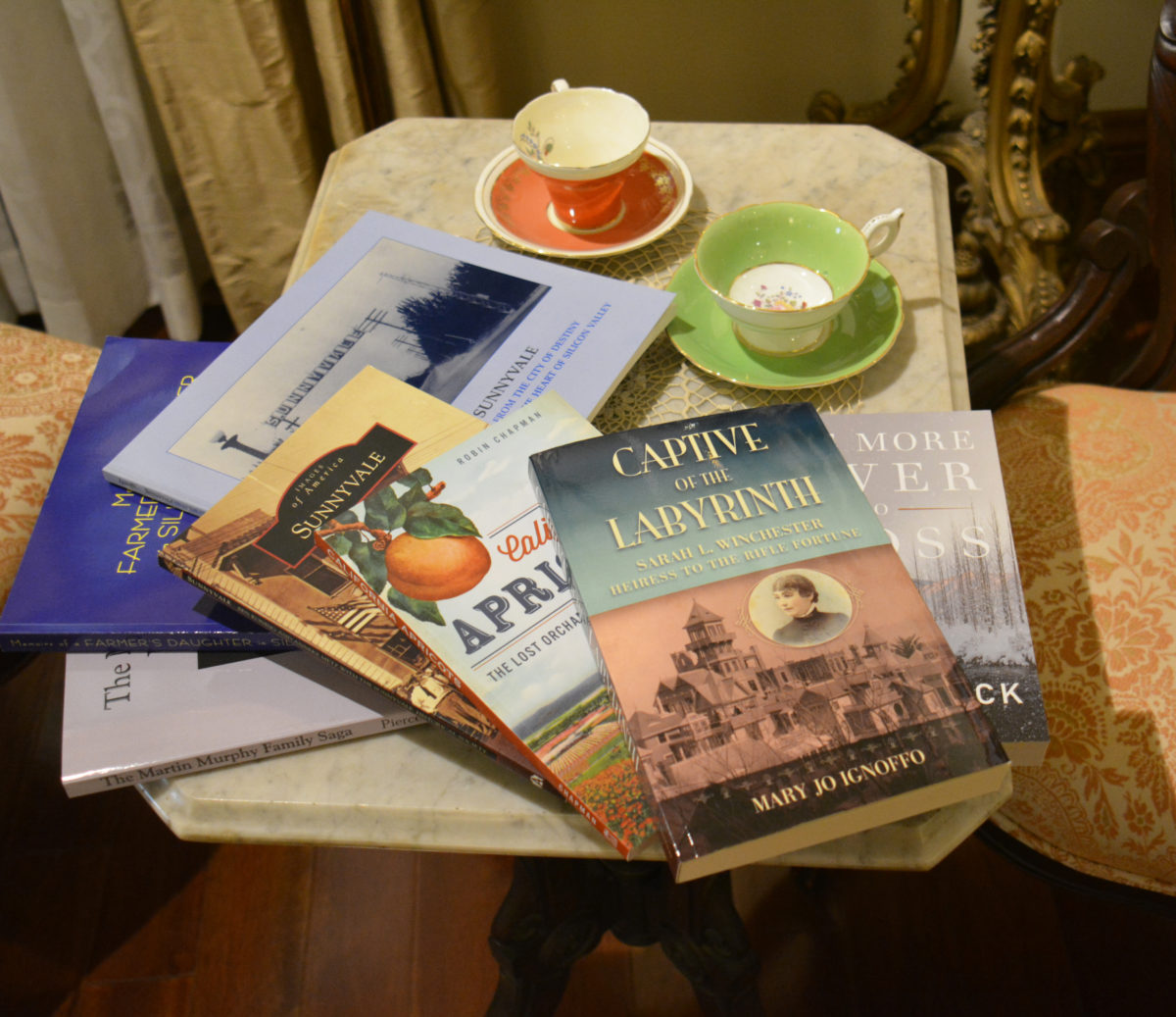 Books lay on a table with vintage tea cups, on sale at the Museum Store