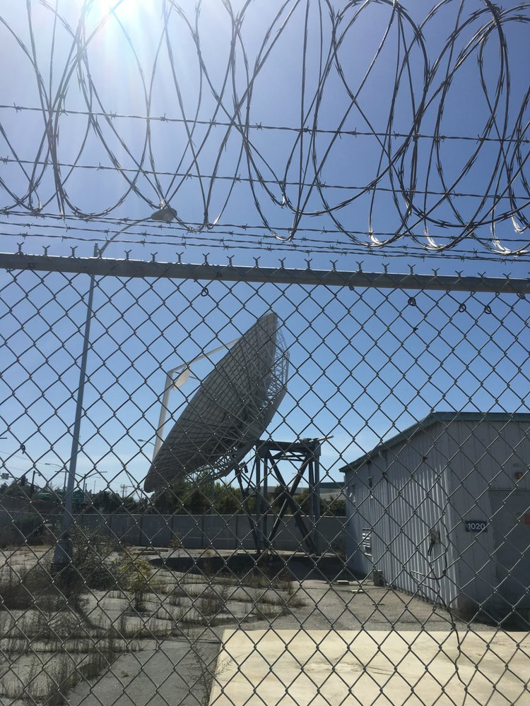 An old satellite is seen through fencing and barbed wire - Onizuka AFB