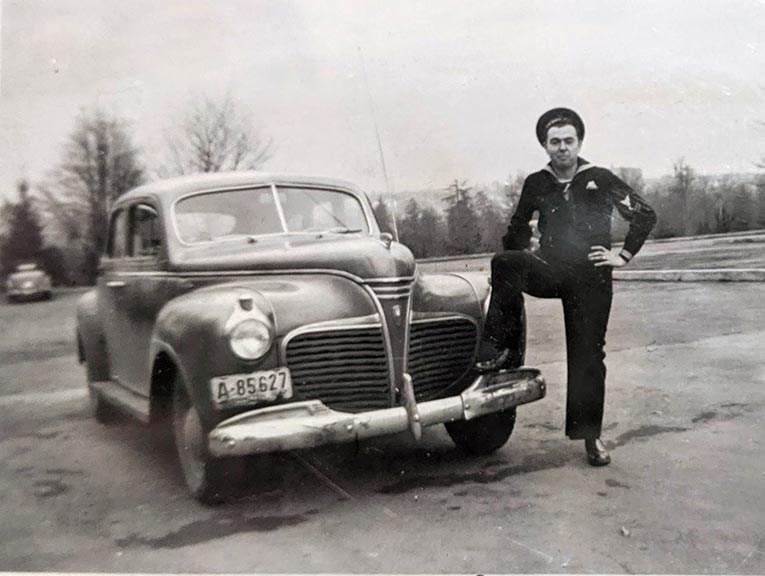 A black and white photo of a man dressed in a military uniform, standing by his car, circa WWII